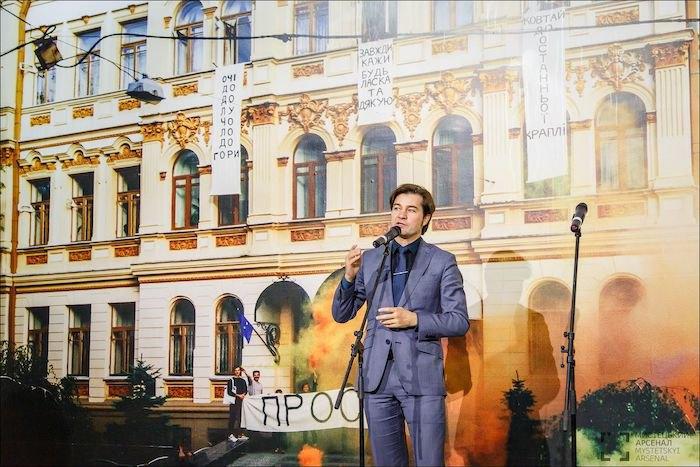 Євген Нищук на відкритті Бієнале молодого мистецтва на тлі документації акції Міті Чурікова