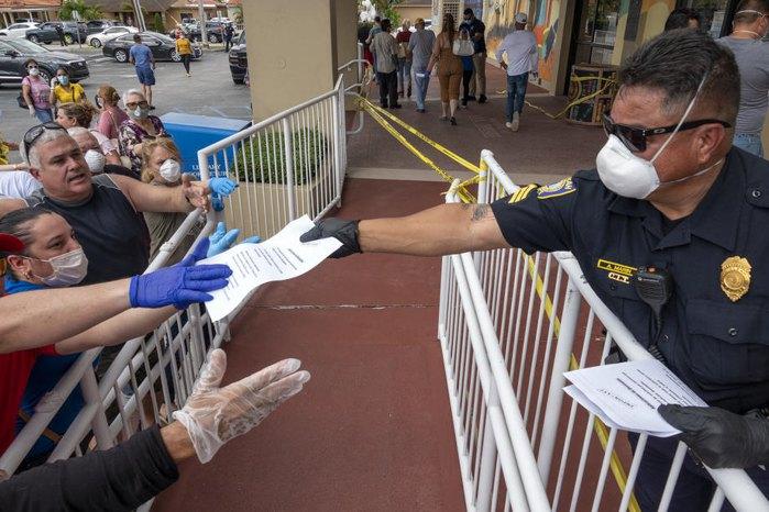 Поліцейський роздає бланки для отримання допомоги по безробіттю, Хайалія, Флорида, США, 7 квітня 2020