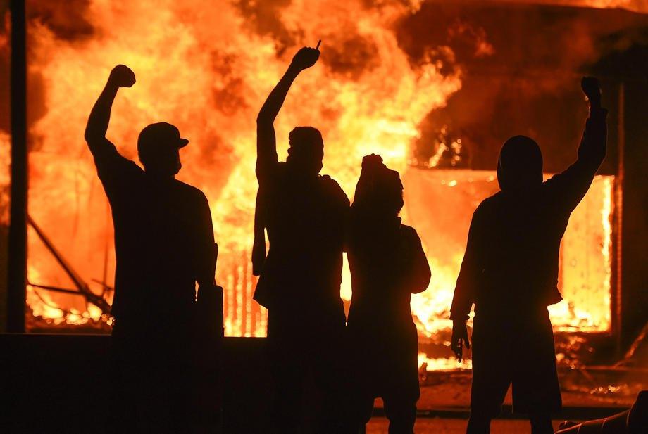 Демонстранты возле подожженного магазина во время беспорядков в Миннеаполисе, 29 мая 2020