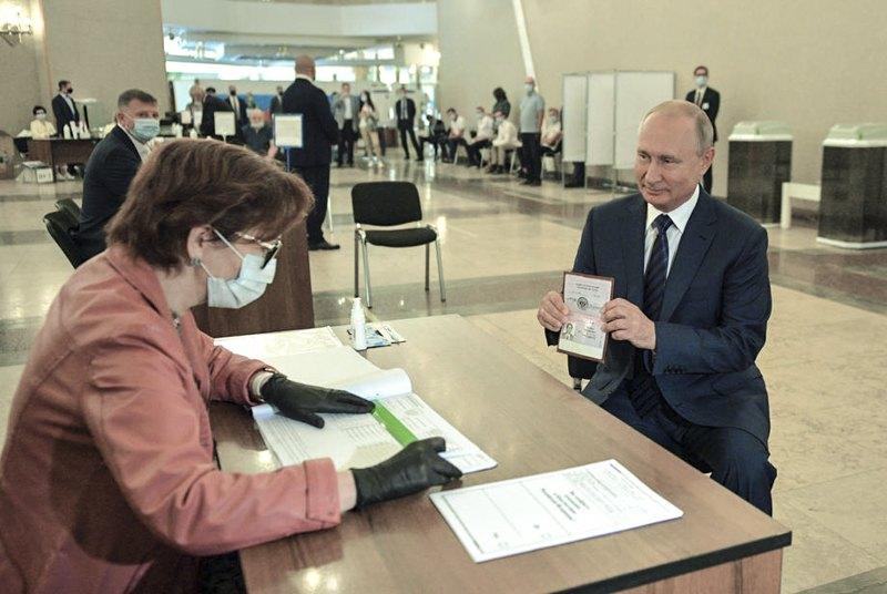 Президент РФ Путiнпоказує свій паспорт під час голосування на виборчій дільниці в Москві, 1 липня 2020.