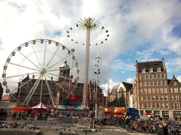 Dam Square (Dam Plein) - главная площадь Амстердама - с шумным парком аттракционов