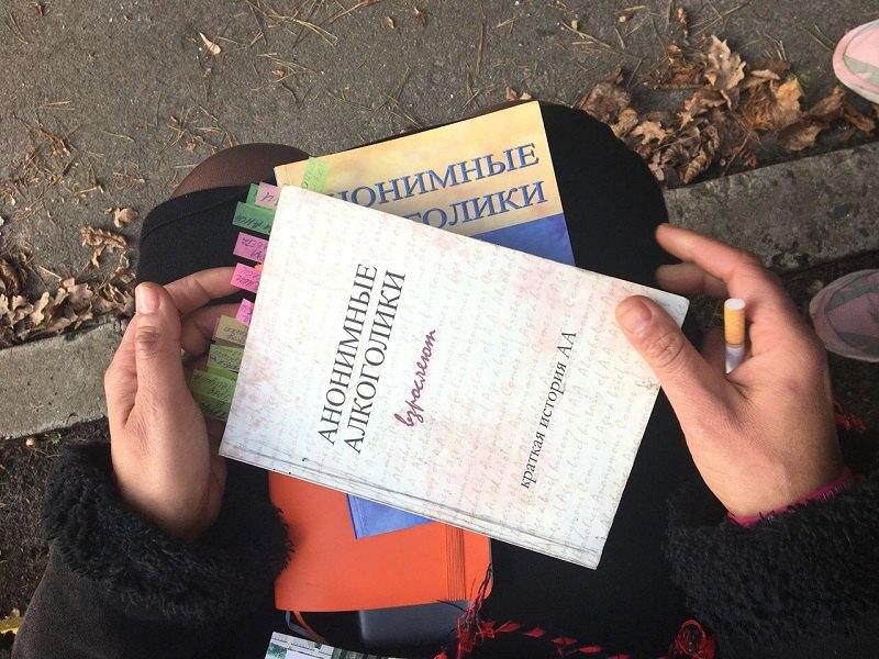 Марія тримає на колінах книжки про історію груп АА