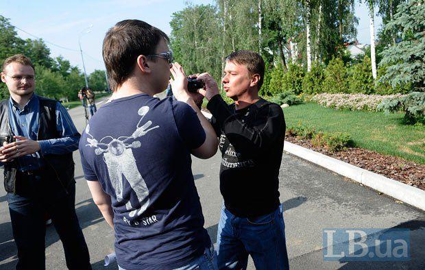 Журналист(слева) пытается выяснить личность неизвестного мужчины, ведущего видеосъемку происходящего