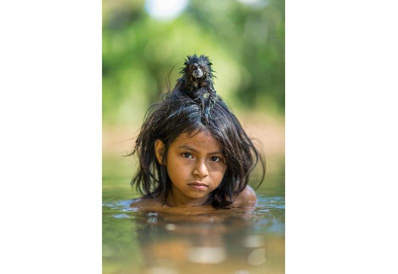 Девочка из племени Мачигенга с прирученным тамарином (обезьянкой) на голове во время купания в реке в национальном парке Ману, Перу.