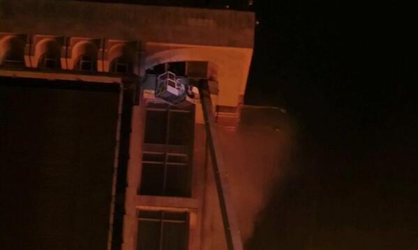 Спасательный кран поднимают к последнему этажу дома профсоюзов, чтобы спасти оттуда людей