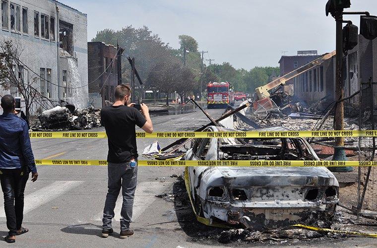 Местные жители делают снимки последствий беспорядков в четверг.