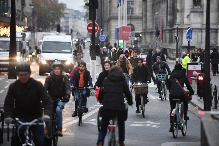 Французы едут на велосипедах на работу во время национальной забастовки транспорта, улица Риволи возле мэрии в Париже, Франция, 5 декабря 2019.
