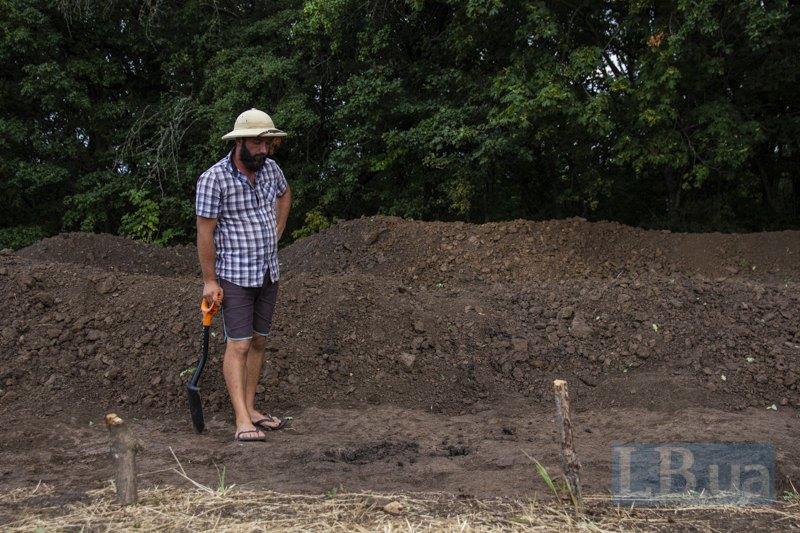 Aрхеолог позначає на шарі землі сліди-ознаки можливих знахідок.