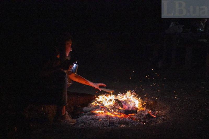 Лєна підкидає дрова у вогнище.