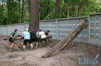 В Пущі-Водиці пройшла акція проти ЖК посеред лісу: бетонний паркан пробили колодою