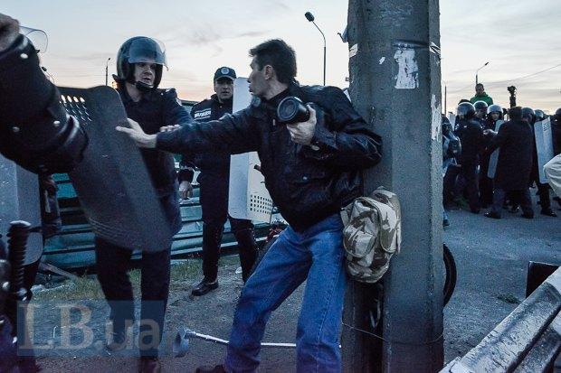 Милиционер в не особо вежливой форме отталкивает фотографа, который передвигается с помощью костиля.
