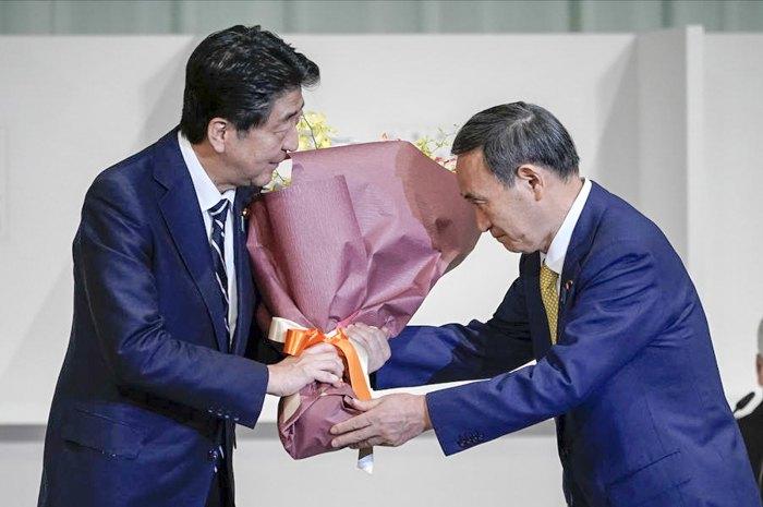Главный секретарь кабинета министров Ёсихидэ Суга вручает цветы уходящему премьер-министру Японии Синдзо Абэ после того, как Суга был избран новым главой правящей партии Японии, Токио, 14 сентября 2020