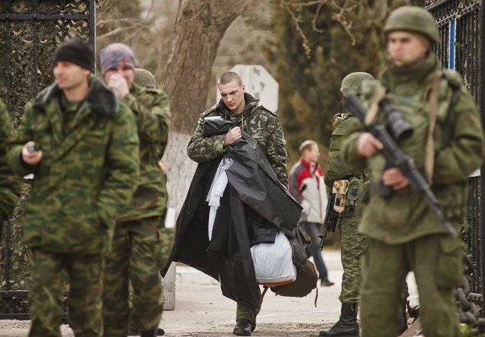 Украинские солдаты покидают территорию украинской воинской части, которая уже находится под контролем *зеленых человечков* Севастополь, 19 марта 2014 года.