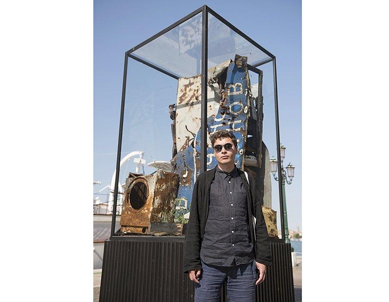 Никита Кадан на фоне своей работы *Трудности профанации*