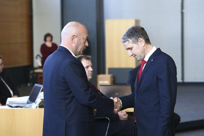 Новоизбранный премьер-министр Тюрингии Томас Кеммерих (слева) и Бьерн Хекке (АдГ) обмениваются рукопожатиями после региональных выборов в Тюрингии, Эрфурт, Германия, 5 февраля 2020.