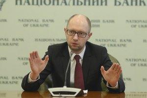 Яценюк пояснив низький курс гривні російськими танками на кордоні