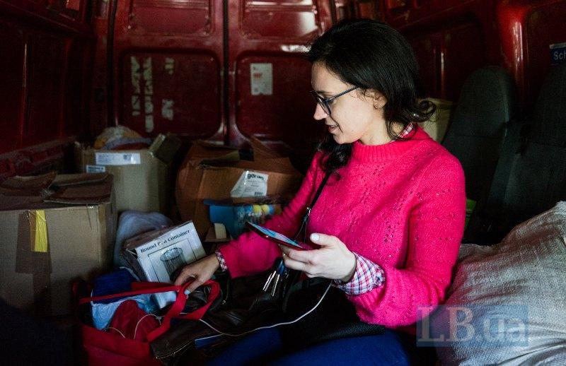 Лєна тримає пакунки з фарбами і водночас координує роботу фонду