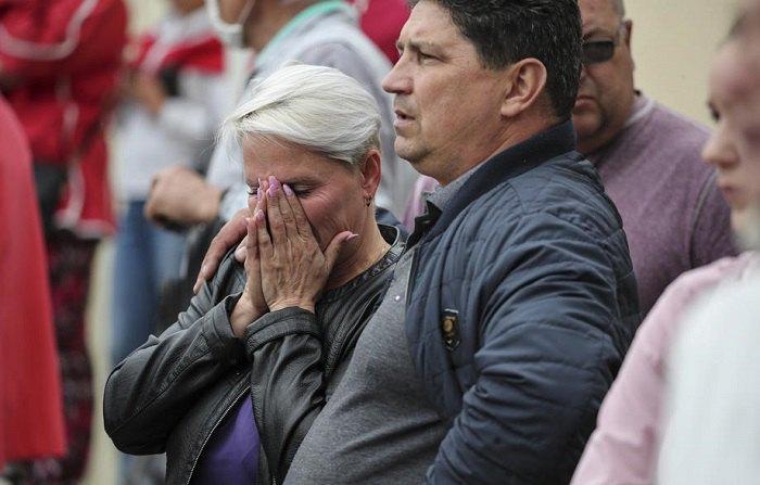 Люди стоят стоять біля ізолятора тимчасового утримання, де затримані їхні родичі, які брали участь в акціях протесту