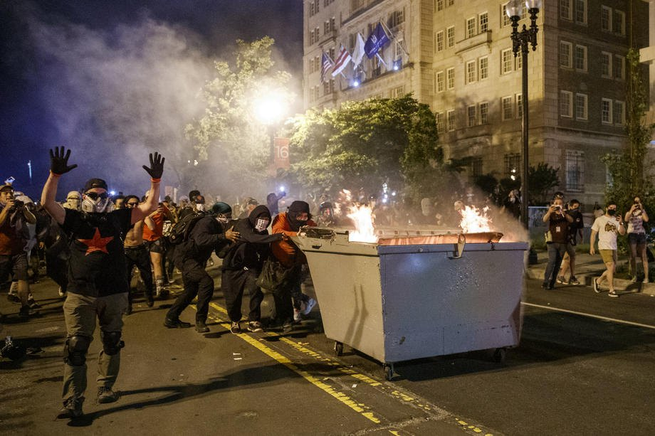 Демонстранты толкают горящий мусорник навстречу полиции во время протестов возле Белого дома в Вашингтоне, 30 мая 2020.