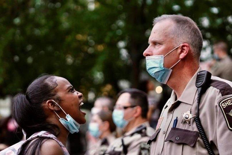 Женщина кричит на заместителя шерифа во время протестов в Миннеаполисе, 28 мая 2020