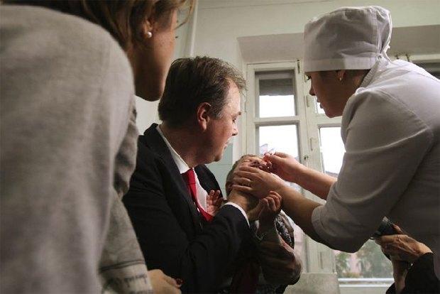 Замминистра охраны здоровья Игорь Перегинец участвует в процессе вакцинации ребенка