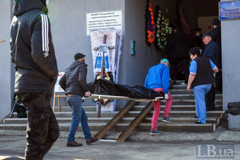 До головного входу привезли ще одне тіло . Інші працівники спокійно спостерігають за процесом.
