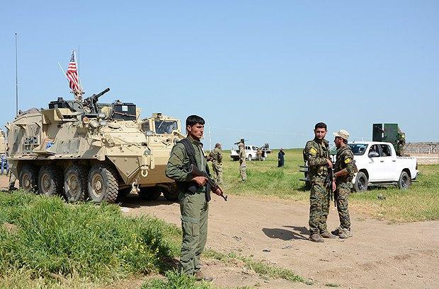 Солдаты милиции Курдистана (YPG) рядом с военными машинами США недалеко от г.Дарбасия на сирийско-турецкой границе, Сирия, 29 апреля 2017.