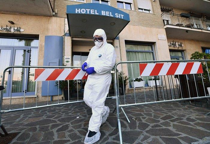 Медпрацівник у захисному одязі виходить з готелю Bel Sit в Аласіо, де 34 людини перебувають на карантині, Італія, 26 лютого 2020.