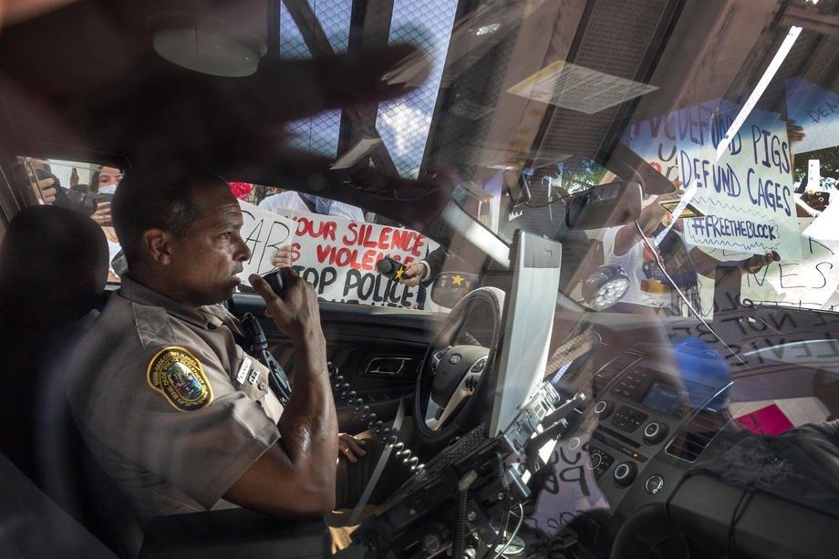 Офицер департамента полиции Майами в своей машине в окружении протестующих, во время протестов в Майами, Флорида, 30 мая 2020