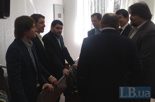 Сыновья Щербаня - слева, адвокат старшего сына(крайний справа) и Виталий Гайдук со спины беседуют во время перерыва