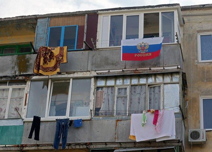 Российский флаг висит на балконе жилого дома в Севастополе