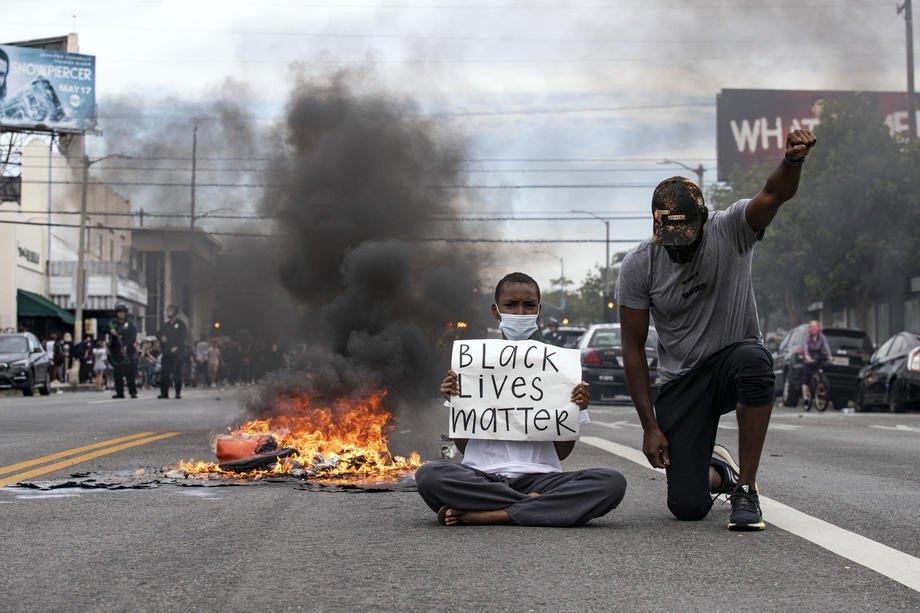 Протестующий держит плакат с надписью «Жизни темнокожих имеют значение» во время протестов в Лос-Анджелесе, штат Калифорния, США, 30 мая 2020 года.