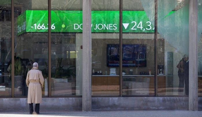Прохожий наблюдает за электронным табло индексов Dow Jones, S & P и Nasdaq возле офиса Fidelity Investments в Бостоне, штат Массачусетс, США, 9 марта 2020.