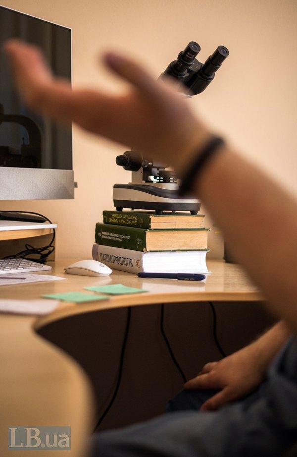 """Робоче місце, мікроскоп та книга """"Патоморфологія""""."""