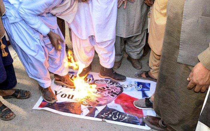Демонстранти спалюють плакат президента Франції Макрона під час акції в Пакистані, 26 жовтня 2020 р.