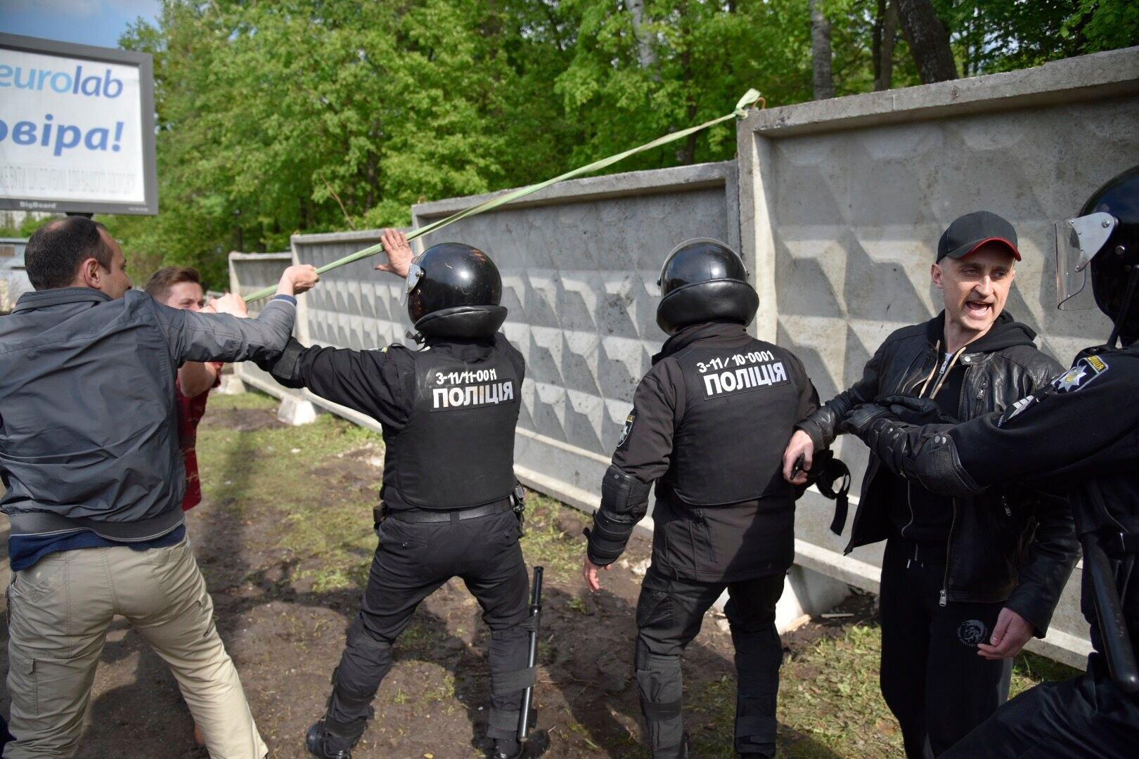 Мужчина в кожаной куртке координирует действия титушок и людей в полицейской форме.