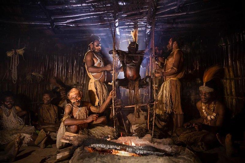 Семеро мужчин из семьи Гемтасу наблюдают за процессом мумификации. Тело поворачивают над огнем. Никому из участвующих в церемонии не разрешается уходить или мыться.