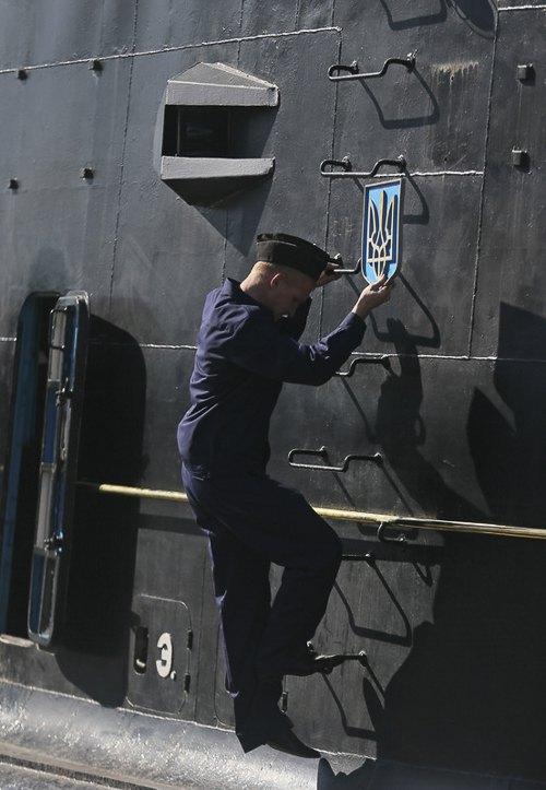 Моряк ВМФ России снимает государственный герб Украины с украинской подводной лодки *Запорожье* на базе ВМФ Украины в Севастополе, Крым, Украина, 21 марта 2014.