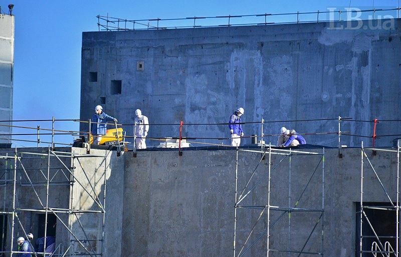 Рабочие в белых робах строят технологическое здание, примыкающее к саркофагу