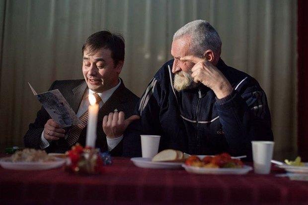Юрий Лифансе(слева) с бездомным во время традиционного благотворительного обеда для бездомных на Рождество