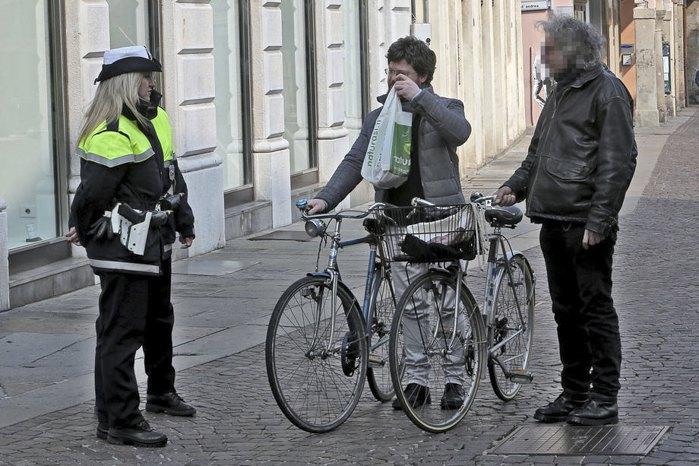 Офіцер поліції уточнює мету прогулки пішоходів на вулиці міста Падуя через надзвичайну ситуацію з коронавірусом в Італії, 12 березня 2020