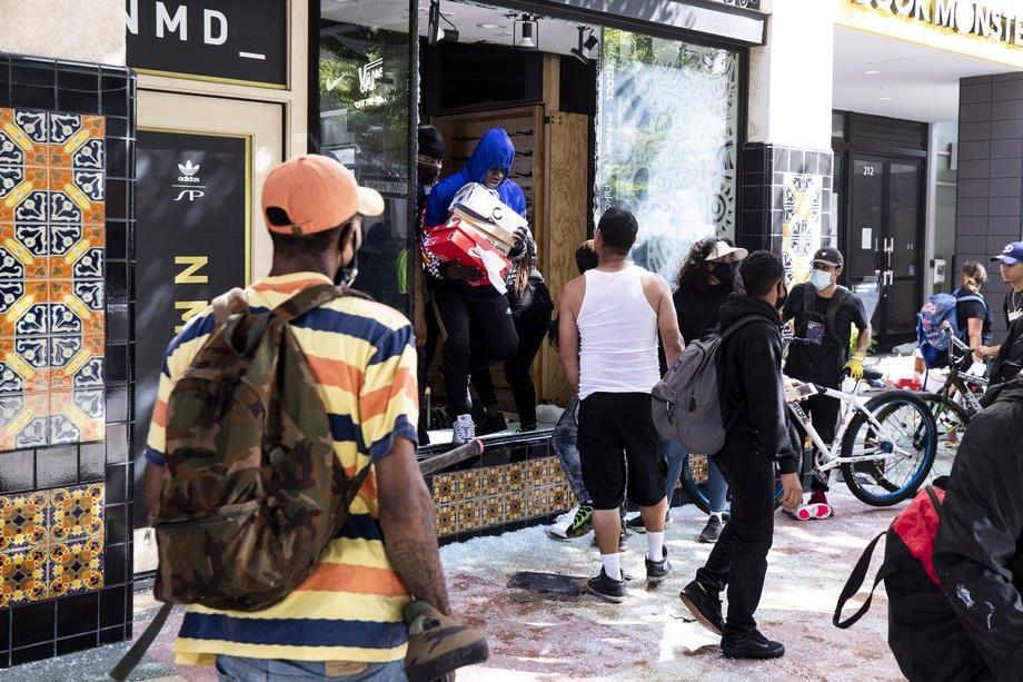 Мародер выходит из обувного магазина во время протестов в Санта-Монике, штат Калифорния, 31 мая 2020 года.