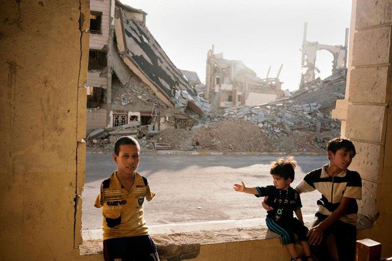 Семья иракских беженцев среди обломков в разрушенном городе Рамади.