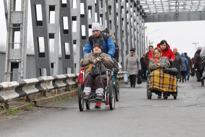 Люди переходять по відновленому мосту у Станиці Луганській