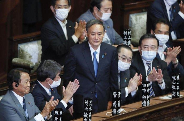 Коллеги аплодируют Ёсихидэ Суга после его избрания премьер-министром Японии на заседании парламента в Токио, 16 сентября 2020 .