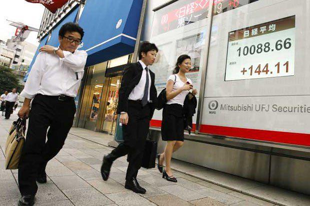 Японцы идут мимо экрана с индексом Nikkei. В 2009 году он начал было активно расти, и у Японии появилась надежда на выход из затяжного кризиса