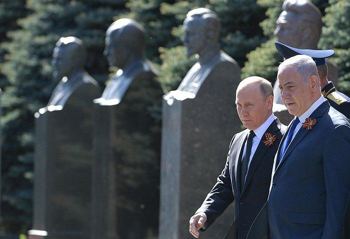 Путин и Нетаньяху общаются перед началом военного парада в Москве, 09 мая 2018.