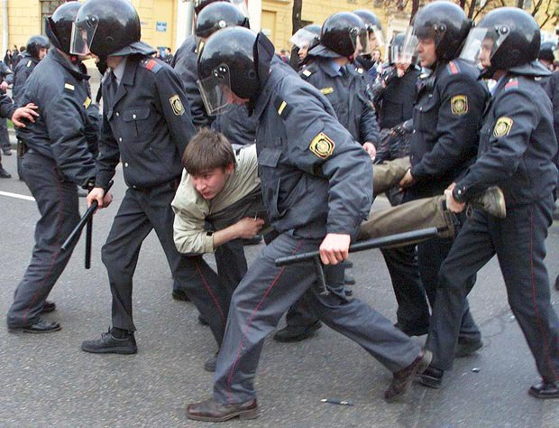 Беларусский ОМОН арестовывает демонстранта во время антиправительственного митинга в Минске, 19 апреля 2002 года.