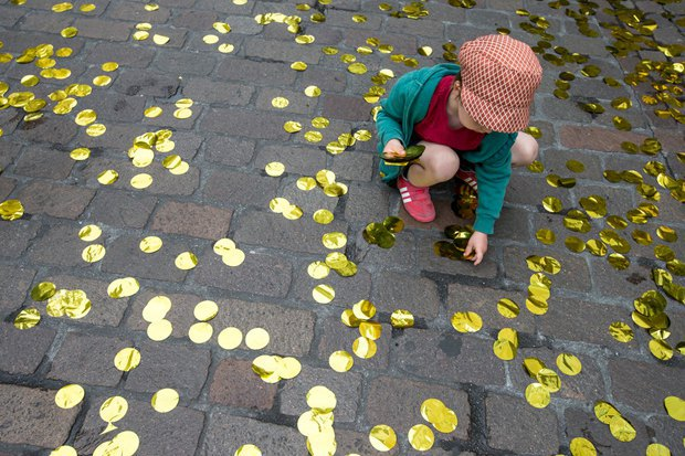 Дівчинка в Базелі збирає золоте конфетті, що символізує гроші, які отримувавали б швейцарці в разі ухвалення пункту про базовий дохід на референдумі