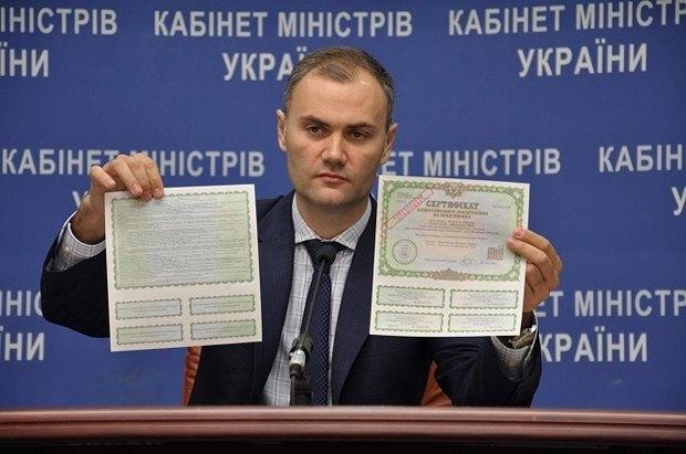 Министр финансов Юрий Колобов показывает образцы сертификатов казначейских обязательств для граждан